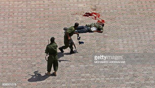 Two members of the AMISOM forces stand past the body of which is believed to be an Islamist rebel who attacked the Mogadishu hotel on September 12...
