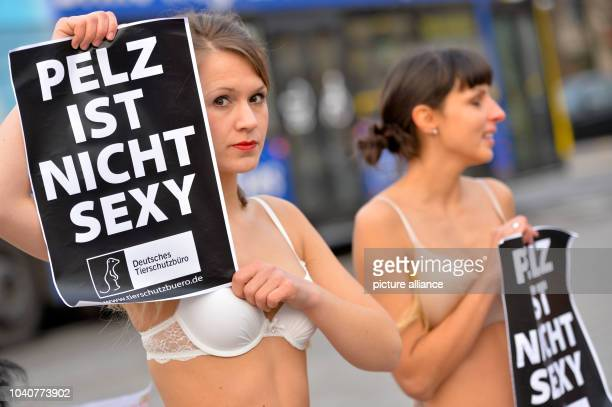 Two members of the animal protection organisation 'Deutsches Tierschutzbüro' stand in front of a tent of the MercedesBenz Fashion week at the...