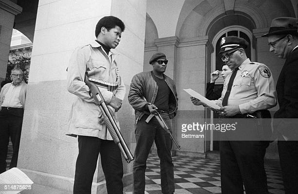 Two members of the Black Panther Party are met on the steps of the State Capitol in Sacramento, May 2 by Police Lt. Ernest Holloway, who informs them...