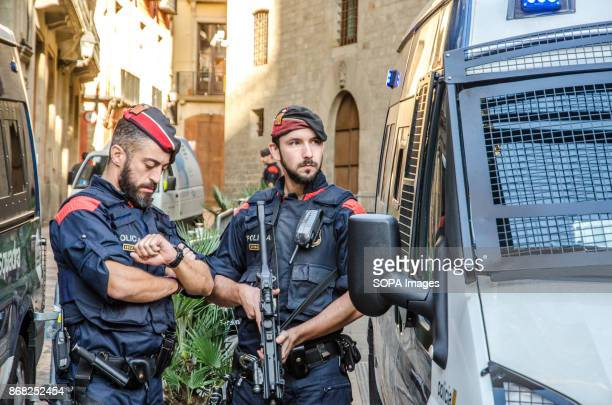 Two members of the Catalan police seen guarding the entrance to the Palace Throughout the morning a large group of media have gathered at the plaza...