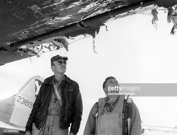 Two members of the crew looking at their seriously damaged B17 bomber after a raid on Debieczen in Hungary Italy 21 September 1944