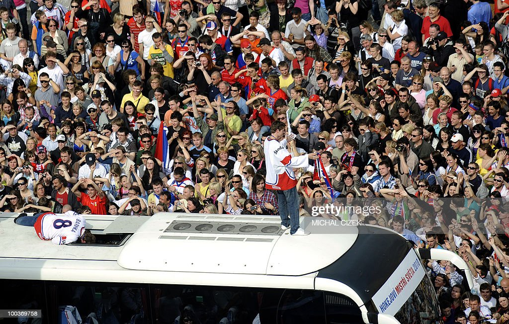 Two members of the Czech Ice hockey team stand on the roof of a bus to celebrate with their fans on the Old Town Square on May 24, 2010 in Prague. The Czech hockey team returned from Cologne (Germany) where they won the ice hockey World Championships beating the Russians 2-1.