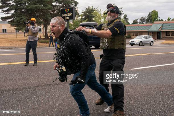 Two members of the far-right group Proud Boys react to an attack by left-wing counter protesters on August 22, 2021 in Portland, Oregon. The Proud...