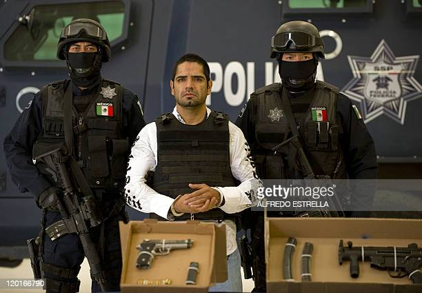 Two members of the Federal Police escort Jose Antonio Acosta aka 'El Diego' one of the Juarez Cartel leaders during the presentation to the media at...