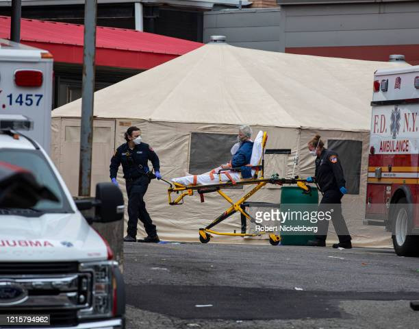 Two members of the Fire Department of New Yorks Emergency Medical Team wheel in a patient with potentially fatal coronavirus to the Elmhurst Hospital...