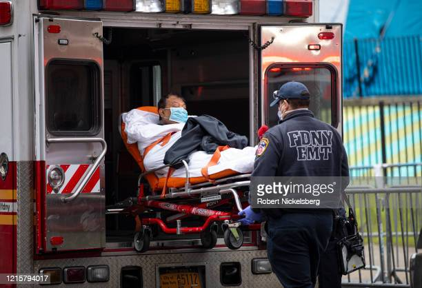 """Two members of the Fire Department of New York""""u2019s Emergency Medical Team wheel in a patient with potentially fatal coronavirus to the Elmhurst..."""