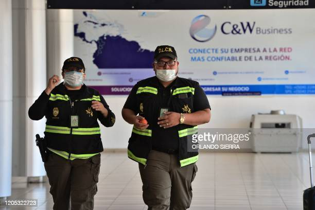 Two members of the Honduran Directorate for the Fight against Drug Trafficking wear protective face masks as a precaution against the spread of the...
