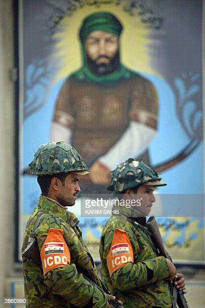 Two members of the Iraqi Civil Defence Corps stand guard in front of a picture of Imam Ali cousin and brotherinlaw of Prophet Mohammed and Islam's...