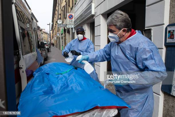 Two members of the Italian Red Cross sanitize an ambulance parked in front of the local Red Cross Committee on February 18, 2021 in Bergamo, Italy....