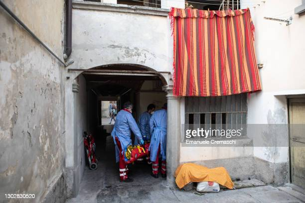 Two members of the Italian Red Cross, wearing PPE , lift an elderly woman lying on an inflatable stretcher up on the stairs of her home on February...