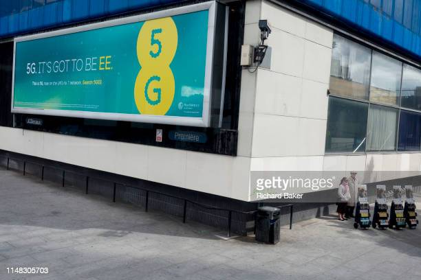 Two members of the Jehovahs Witnesses stand around the corner to a large billboard ad for phone provider EE's new 5G, the first provider to offer the...