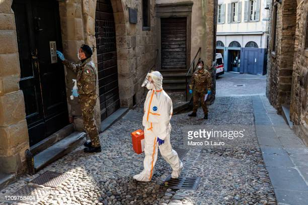 Two members of the military order of the Italian Red Cross escort in an alley of the old city, a member of the Italian Red Cross during his round of...