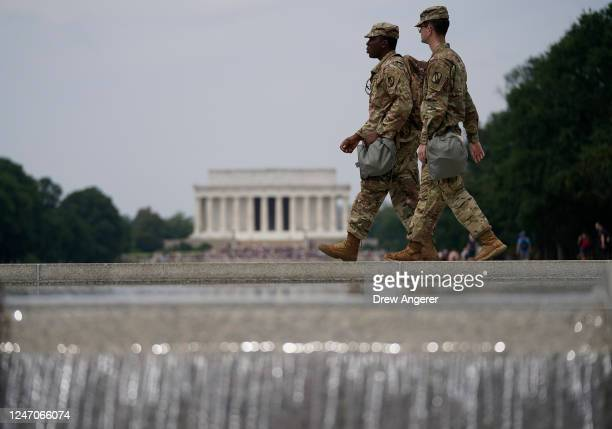 Two members of the National Guard walk past at the World War II Memorial as protests against police brutality and racism take place on June 6, 2020...