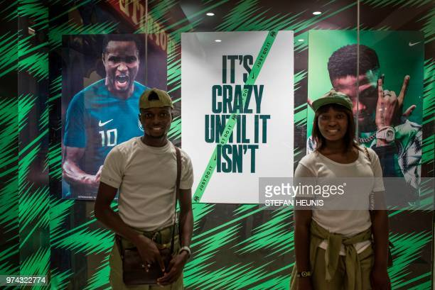 Two members of the Nigerian National Youth Service Corps pose for a picture in front of a Nike store in Lagos on June 4 2018 The Nigeria Super Eagles...