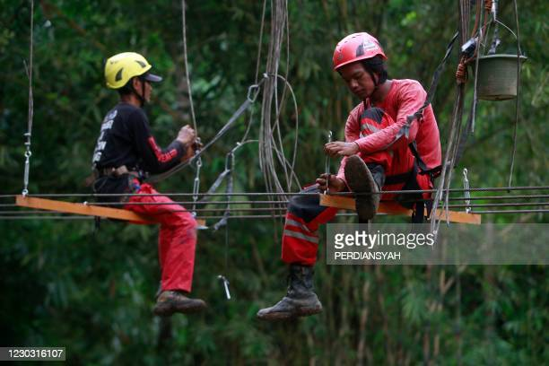Two members of the non-profit organization Vertical Rescue Indonesia help to build a bridge at a village in Bandar Lampung on Indonesia's Sumatra...