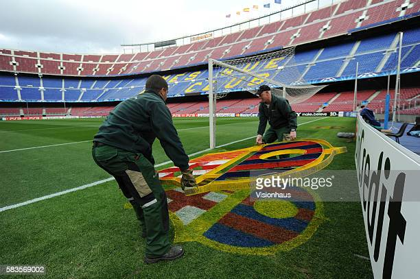 Two members of the Nou Camp groundstaff remove the club crest template after spraying paint on the club crest stenciled on to the grass before the...