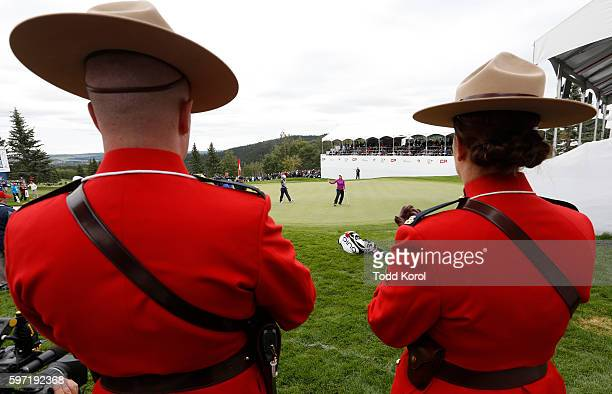 Two members of the Royal Canadian Mounted Police watch Brooke Henderson finish her putt on the 18th hole during the final round of the Canadian...