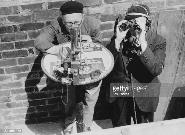 Two members of the Royal Observer Corps scan the sky with a Post Plotting Instrument and binoculars searching for German Luftwaffe aircraft from...