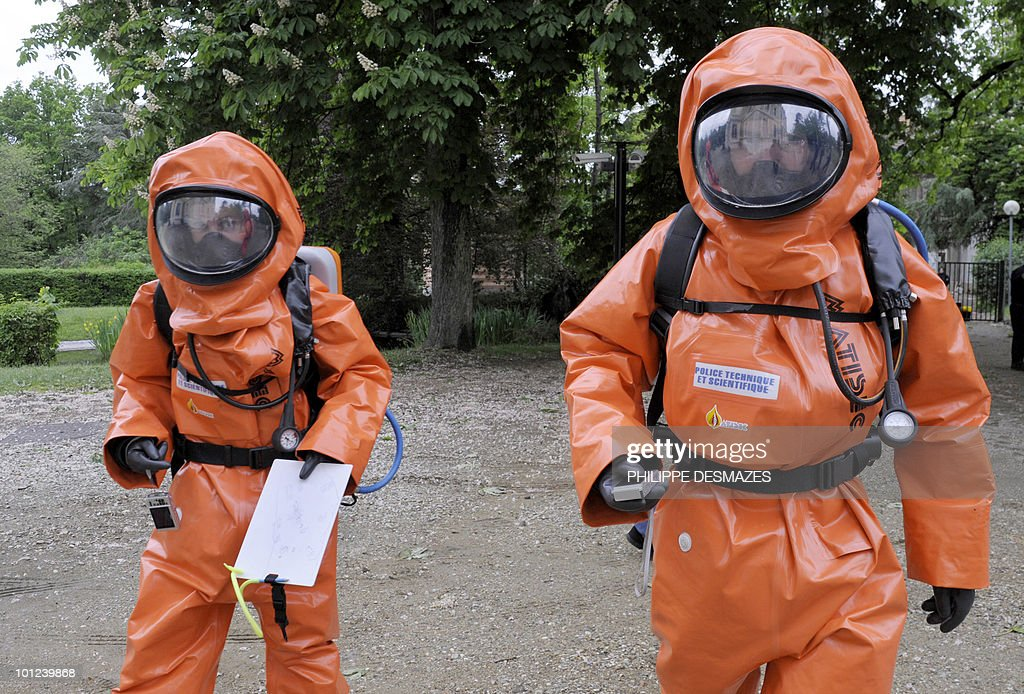 Two members of the scientific police wearing gas and liquid-proof jumpsuits prepare to take part in a simulation of a chemical bomb attack on May 6, 2010 at the Scientific and Technical Police Division headquarters in Ecully, a western suburb of Lyon. This exercice organised by the Central Directorate Judicial Police offers an opportunity to train participants to become specialists in judicial identity and investigators specialized in toxic terrorism, biological warfare or chemical accidents.