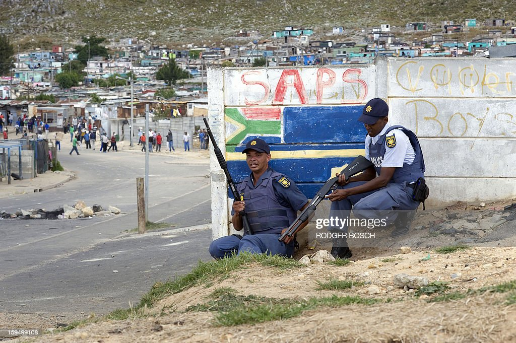 Two members of the South African Police Services(SAPS) takes cover behind a wall from rocks being thrown by protestors during an illegal strike by farmworkers, on January 14, 2012 in Villiersdorp, a small farming town about 100Km North of Cape Town, South Africa. The farm workers have said that they they will not return to work on the fruit growing region's farms until they receive a daily wage of at least R150($17) per day. The colours of the SAPS are painted on the wall behind the officer. BOSCH