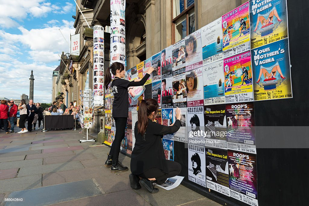Two members of the staff stick posters outside the Spotlites Fringe