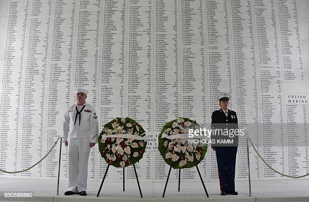 Two members of the US military stand at attention after US President Barack Obama and Japanese Prime Minister Shinzo Abe laid wreaths at the USS...
