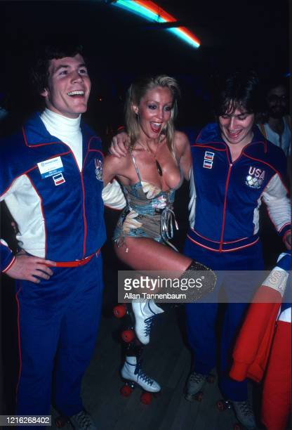 Two members of the US Olympic Men's Ice Hockey Team pose on either side of Cynthia Rixon in a lowcut onepiece outfit at the Roxy Roller Disco during...
