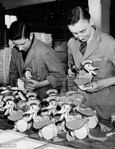 Two men add the finishing touches to a batch of Donald Duck toys which are in great demand for Christmas