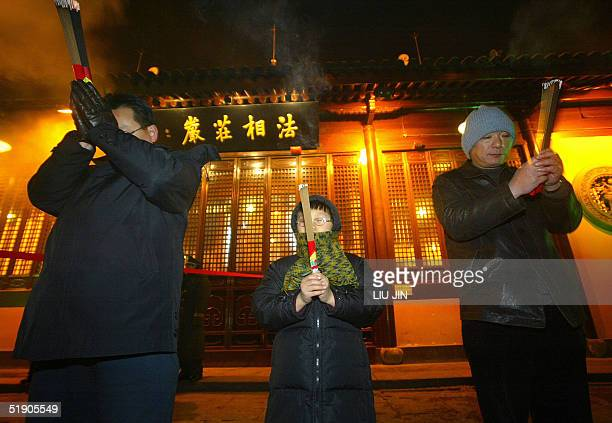 Two men and a boy pray with burning incense during New Year's celebrations at Longhua Temple in Shanghai 01 January 2005 For Chinese when the new...