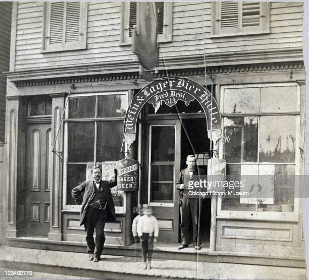 Two men and a little boy stand outside the Wein Lager Bier Halle located at 513 South Halsted Street in Chicago IL 1883
