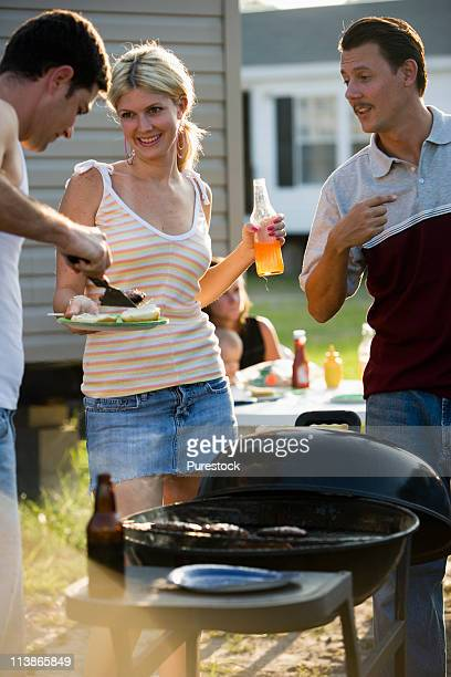 Two men and a woman enjoying a cookout in front of a trailer home