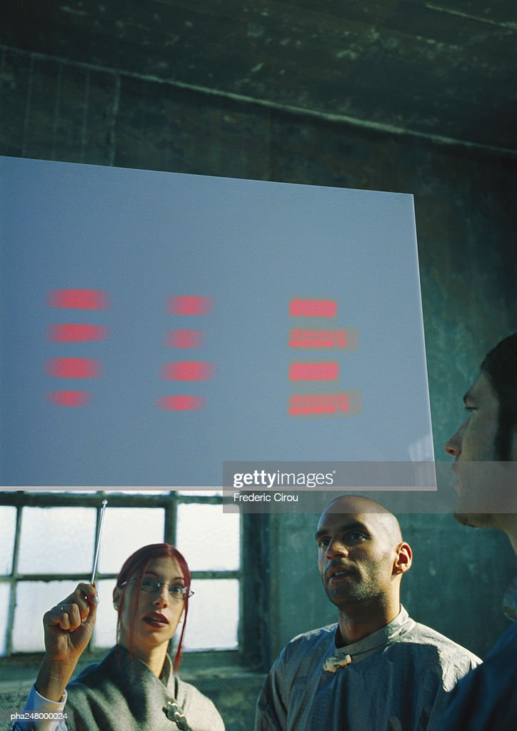 Two men and a woman looking at screen : Stockfoto