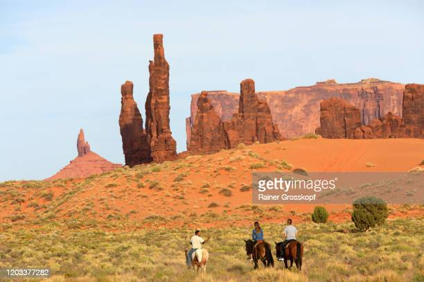 two men and a woman on horses riding in a sandy desert landscape with rock needles - rainer grosskopf fotografías e imágenes de stock