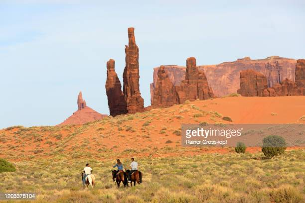 two men and a woman on horses riding in a sandy desert landscape with rock needles - rainer grosskopf stock-fotos und bilder