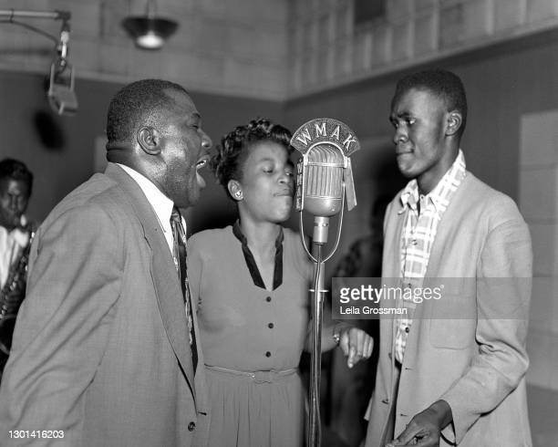 Two men and a woman performs for WMAK radio with a man playing saxophone in the background 1957 in Nashville, Tennessee.