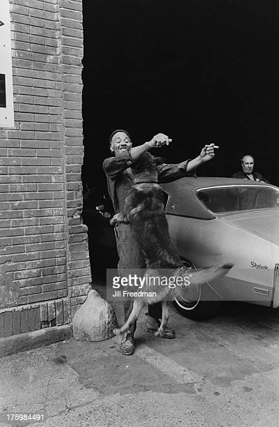 Two men and an enthusiastic dog at a parking garage in Greenwich Village New York 1977