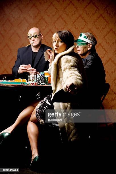 Zwei Männer und glamouröse Frau spielt Poker am Kartentisch