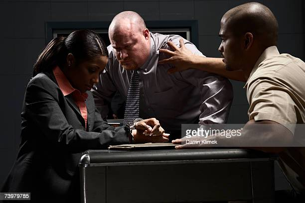 Two men and handcuffed woman at desk in interrogation room