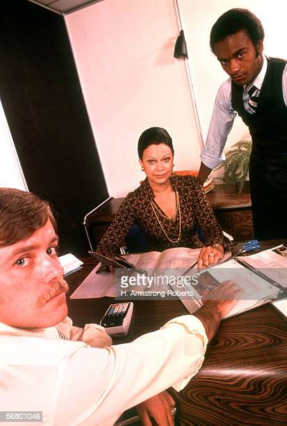 Two men and one woman in office meeting