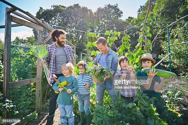 two men and sons holding marrows and rhubarb on allotment - fils de photos et images de collection