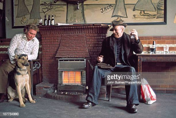 Two men and their dog warm up by a gas fire at a pub in Manchester England in 1976