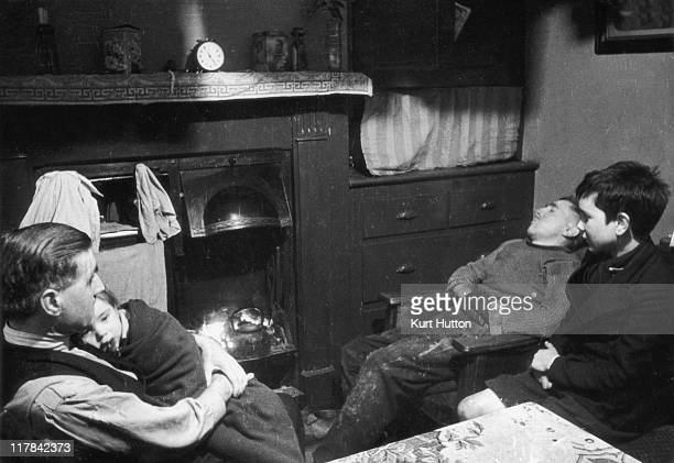 Two men and two children sitting by the fireplace on which sits a kettle in a poor area of Wigan Lancashire England United Kingdom 1939 A small clock...