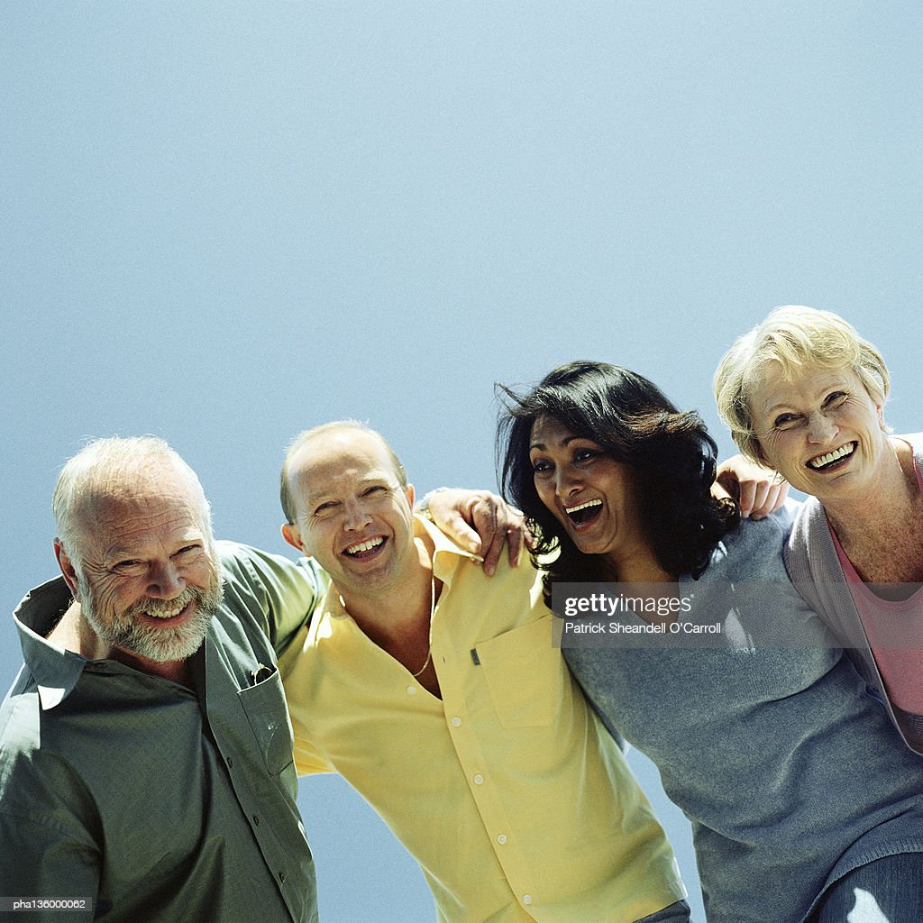 Two men and two women arms around each others' shoulder laughing and smiling : Stockfoto