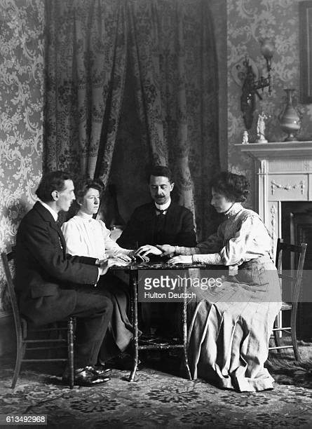 Two men and two women sit around a table during a seance.