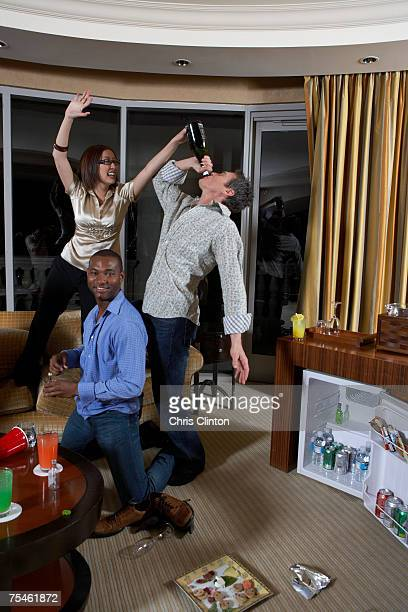 Two men and woman celebrating in hotel room, man drinking from wine bottle