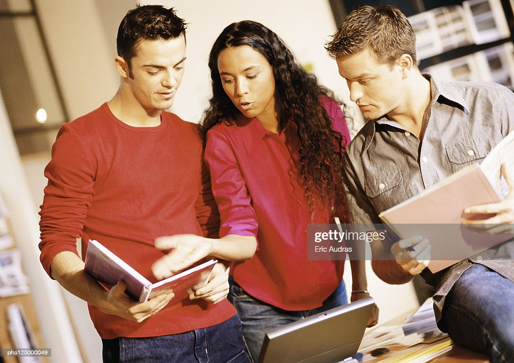 Two men and woman examining documents : Stockfoto