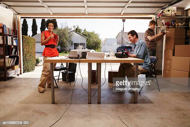 Two men and woman in office space in garage