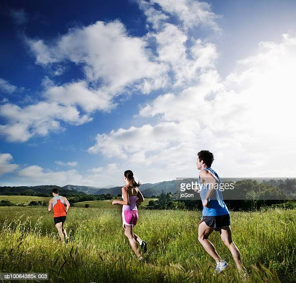 Two men and woman running through grass
