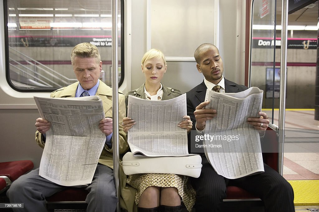 Two men and woman sitting in subway train side by side, reading newspaper : Stock Photo