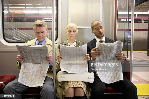 Two men and woman sitting in subway train side by side, reading newspaper